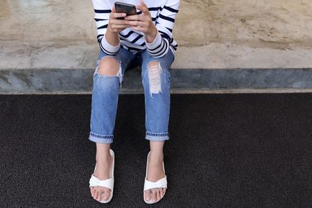 Woman in rip jeans looks at mobile phone.