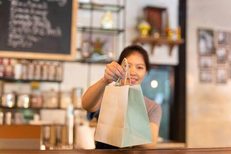 Camarera en el mostrador dando bolsa de papel ecológica con bebida para llevar en la cafetería.