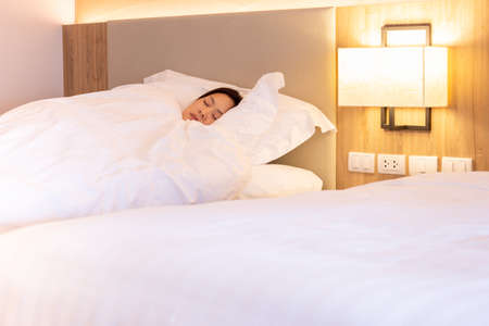 Woman sleeping well in bed with soft white pillow
