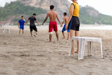 Selected focus group of friends playing soccer on the beach in summertime.