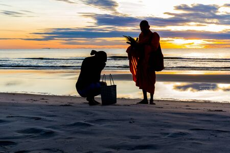 Silhouette of woman ob the sunset beach making merit with food in Thailand. Banco de Imagens