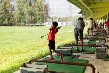 Bangkok Thailand - 27 Jul 2019 Young asian boy with nike trainer logo practicing his golf swing at Srinakarin golf driving range.