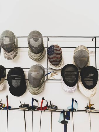 Group of fencing masks and sword hanging on the wall.