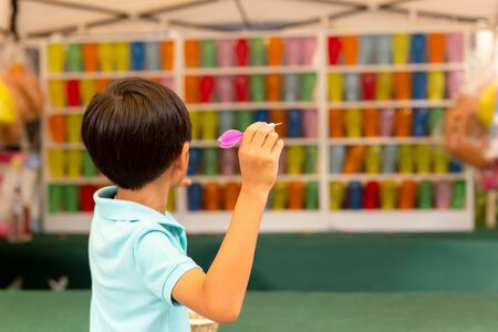 Boy playing the dart game with multicolor balloons at fair. Stock Photo