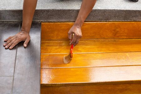 Worker varnishing lacquer on wooden floor outdoors by paint brush.