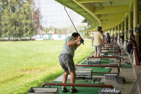 Man practicing his golf swing at golf driving range.