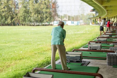 Senior man exercise practicing his golf swing at golf driving range.