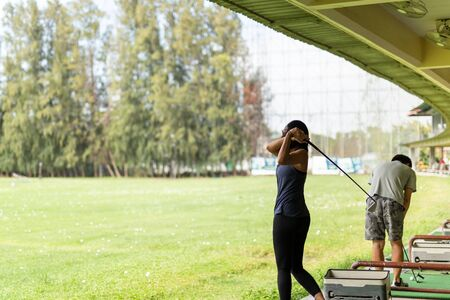 Asian woman practicing his golf swing at the golf driving range.