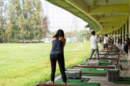 Asian woman practicing his golf swing at the golf driving range. Stock Photo