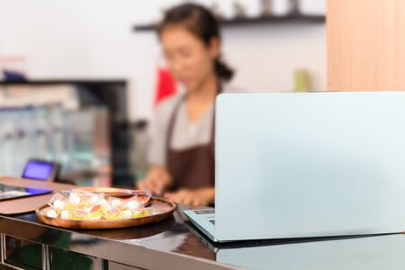 Small business cafe laptop on top counter with woman working