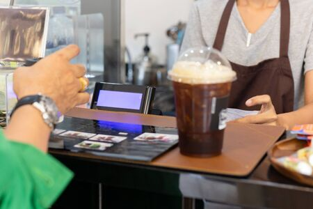 Woman barista serving iced coffee to customer at counter bar in cafe. Stockfoto - 128598002