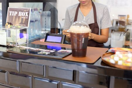 Selected focus cash register with woman barista working behind the counter bar. Stockfoto - 128598013