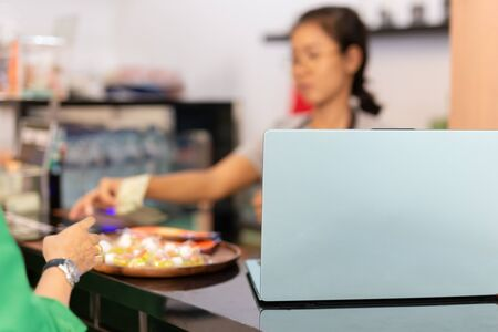 Laptop on top of cafe counter with woman taking money from customer.