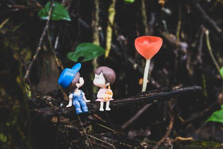 Two little dolls about to kiss sitting under the champagne mushroom.