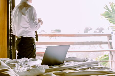 Laptop on the bed with businessman holding cup of coffee looking out hotel room.