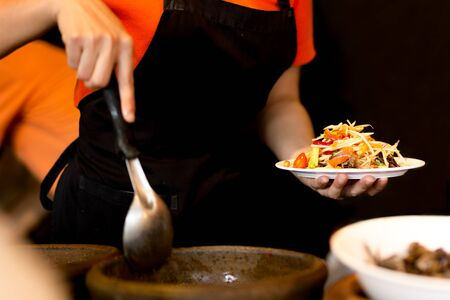 Woman making Thailand spicy papaya salad with crab in restaurant