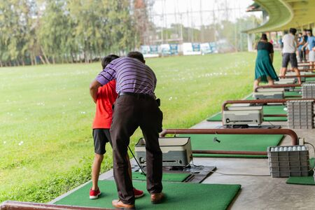 Personal trainer giving lesson to young boy in golf driving range.