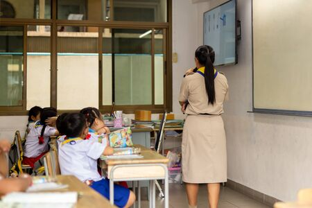 Back view of asian teacher stand in front of class and teaches students.