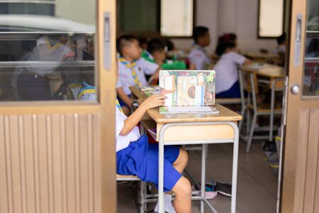 Unidentified children study in the classroom with open book.