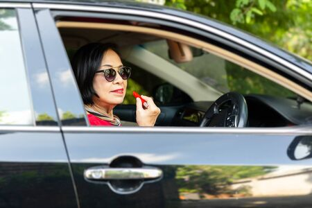 Senior woman with lipstick in her hand sitting in car during a day. 写真素材
