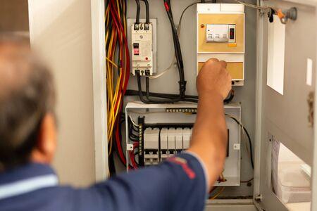 Senior electrician measuring voltage in fuse board. Stock fotó