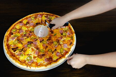 Hand slicing a homemade pizza with pizza cutter on table
