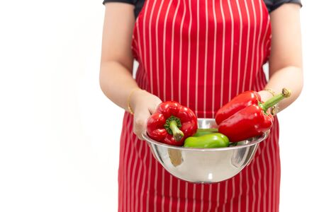 Woman hands holding fresh sweet peppers in a bowl isolated on white background Stock Photo