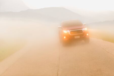 Driving cars in the fog mountain wuth headlight beams in dense mist