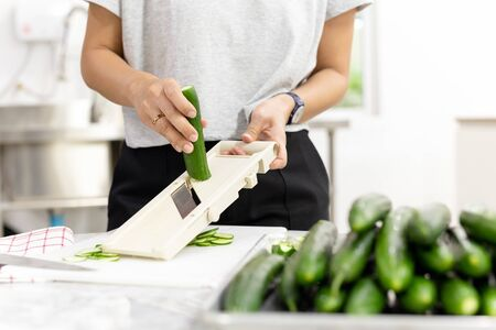 Woman slicing cucumber with vegetable slicer for salad