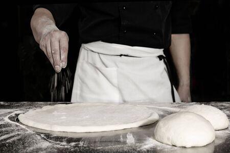 Chef prepares the dough with flour to make a pizza Stock fotó