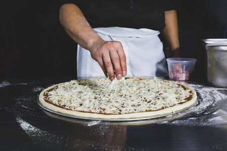 Chefs hand putting cheese on the pizza in black background