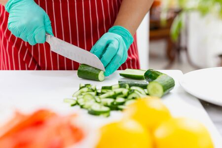 Woman with green glove cutting cucumber in the kitchen on chopping board Banco de Imagens