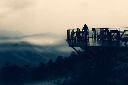 Woman traveler standing outside cafe terrace with beautiful misty mountain view.