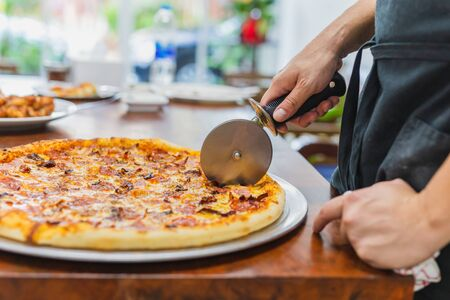 Closeup hand of chef cutting pizza on table