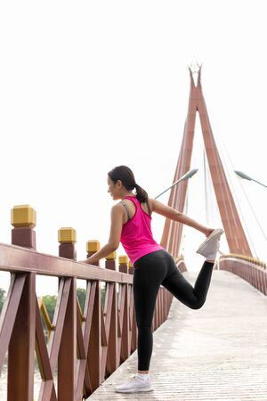 Woman in sportswear stretching her leg on the bridge before doing exercise.