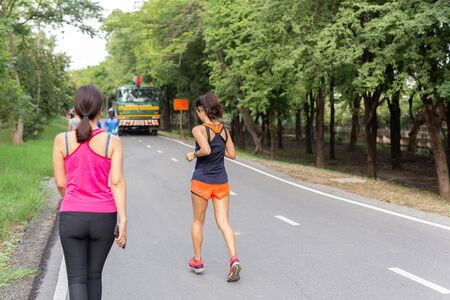 Women jogging on track in park while listening to music on mobile phone. 版權商用圖片