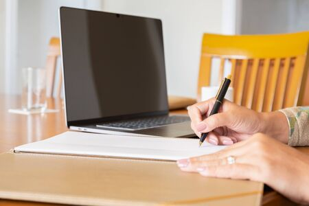 Businesswoman signing document agreement form with laptop on table