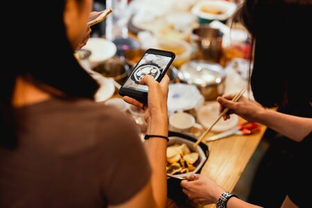 Female Friends having dinner party taking picture of food post on social media. Stock Photo - 133827499