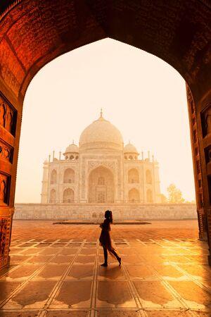 Silhouette unidentified woman tourist walking near Taj Mahal in Agra India.