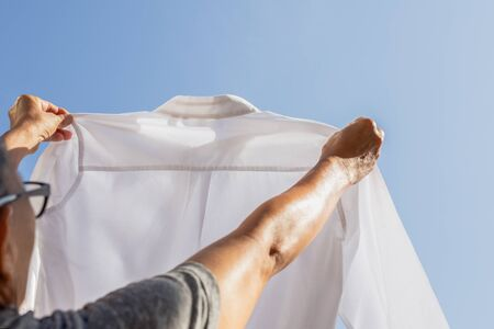 Woman housekeeper holding white shirt checking dirty stain.