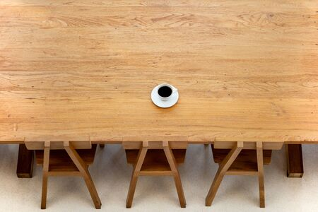 Top view cup of coffee on wooden table with wooden chair in cafe.