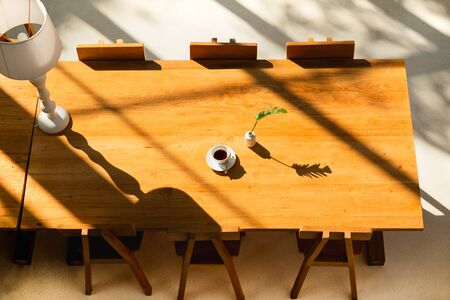 Bright room in the shadows of the sunlight with coffee on wooden table and lamp. Stock fotó