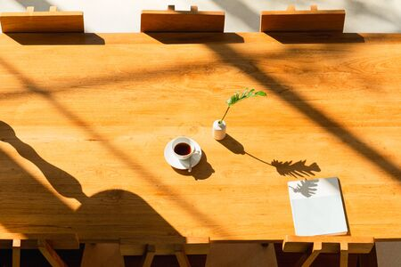 Bright room in shadow of the sunlight with coffee on wooden table and magazine.