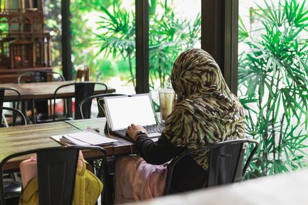 Back view of Muslim woman student in hijab working on laptop at coffee table.