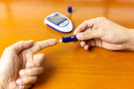 Man using lancelet on finger checking blood sugar level.