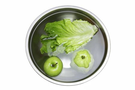 Washing fresh vegetables and fruit in bowl with water