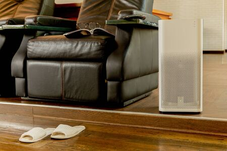 Electric air purifier in a living room for cleaning fine dust in house.