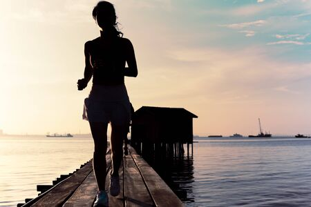 Silhouette of woman jogging in the morning on wooden bridge at sunrise. Stockfoto