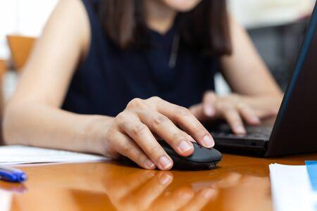 Mano de la empresaria haciendo clic en el ratón trabajando con un portátil