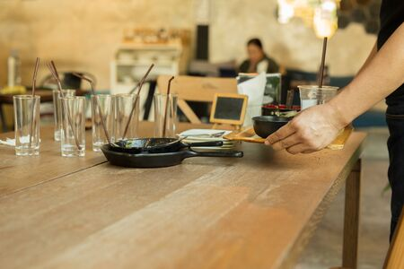 Waiter hand holding tray with dirty dishes in the restaurant